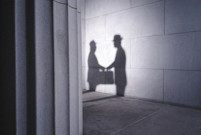 Shadows of two men with briefcase shaking hands, side view